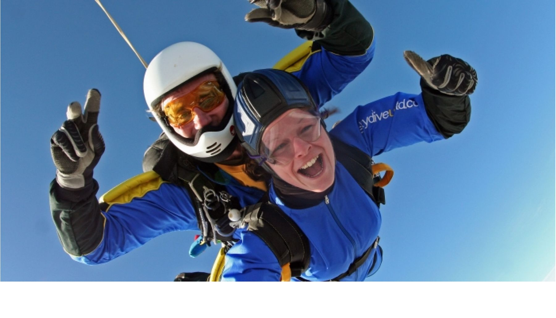 Two people in blue jumpsuits in the sky doing a skydive