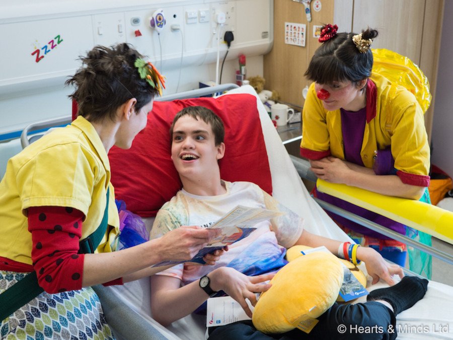 Two Clowndoctors wearing yellow coats stand on either side of a young patient who is smiling at the Clowndoctors from his hospital bed.