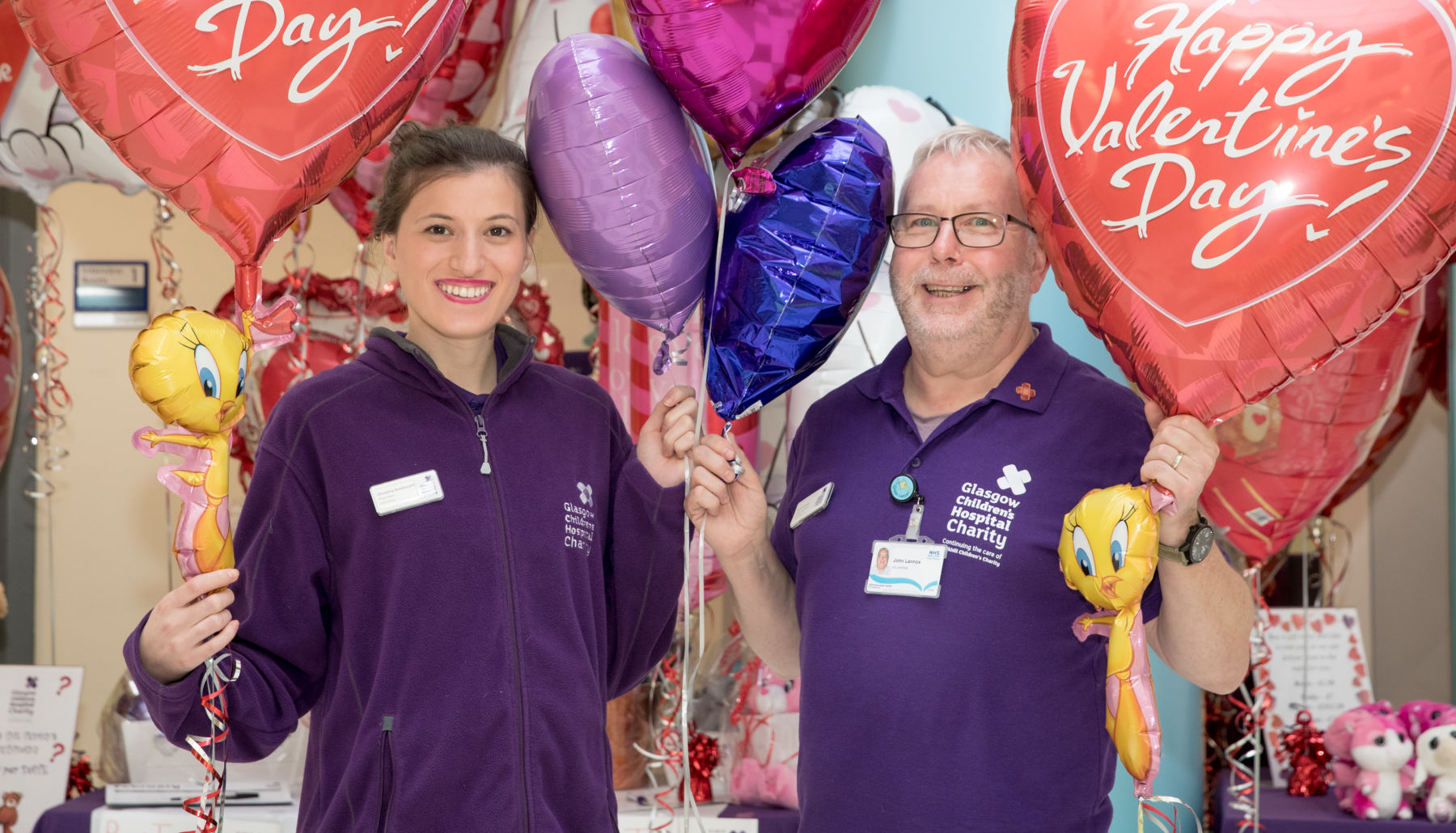 Two volunteers standing smiling at the camera holding large Valentines Day balloons