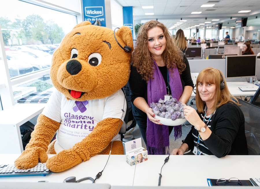 Glasgow Children's Hospital Charity mascot Kami Bear sits at a desk beside two supporters